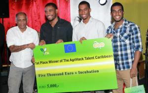 From left, Guyanese Agriculture Minister Dr Leslie Ramsammy presents the first-place prize cheque for 5,000 euros to Matthew Mc Naughton and Jamaican team Node420, at the award ceremony for the Agrihack Caribbean Talent competition in Paramaribo, Suriname, on October 9. Photo courtesy: The Technical Centre for Agricultural and Rural Cooperation ACP-EU (CTA)​.